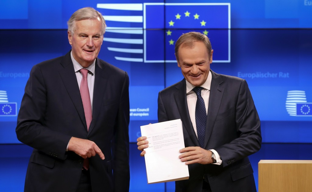 FILE - In this Thursday, Nov. 15, 2018 file photo EU chief Brexit negotiator Michel Barnier, left, delivers the draft withdrawal agreement to European
