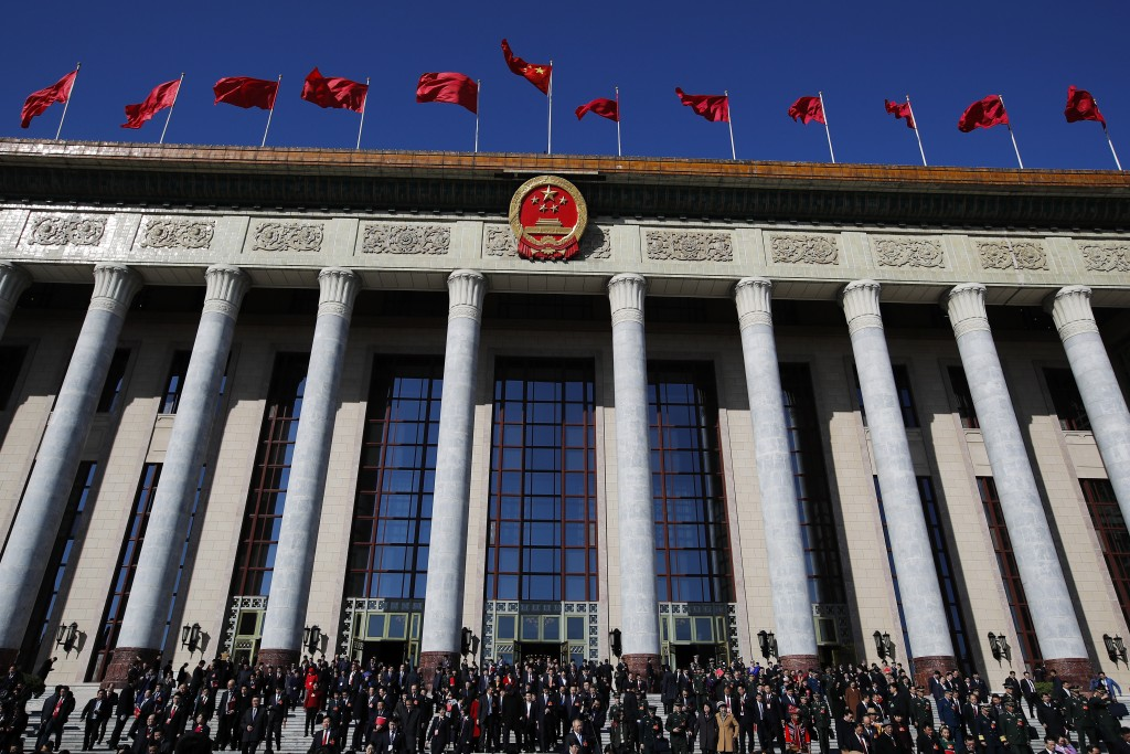 Delegates leave the Great Hall of the People after attending the closing session of China's National People's Congress (NPC) in Beijing, Friday, March