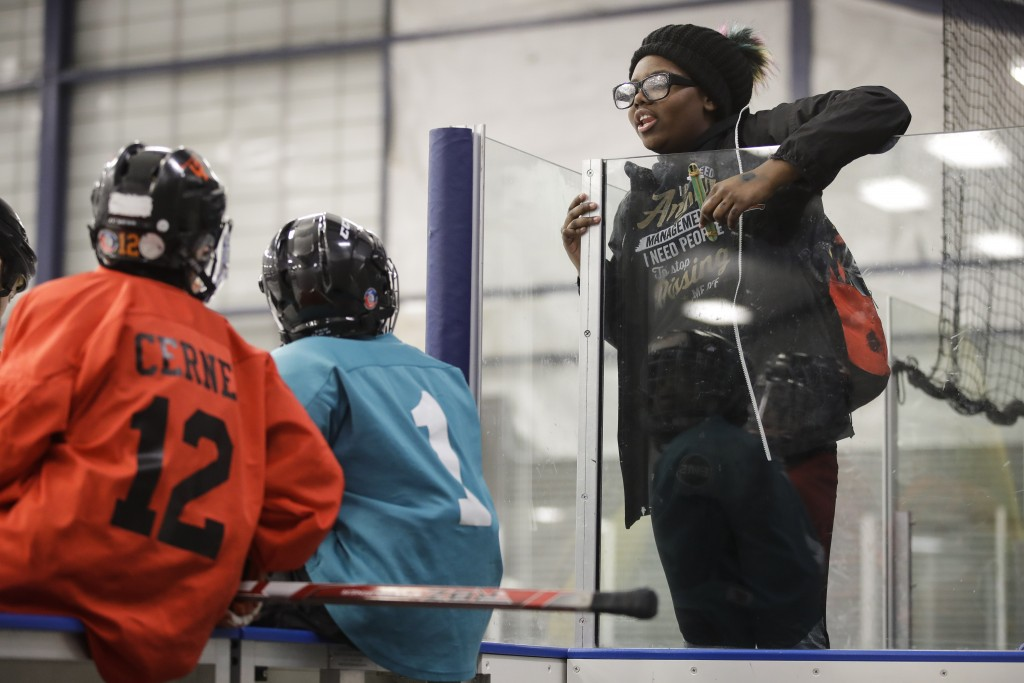 In this Feb. 21, 2019 photo Wylla Johnson, right, talks to her brother Malakye, center left, before he takes part in Snider Hockey practice at the Sca