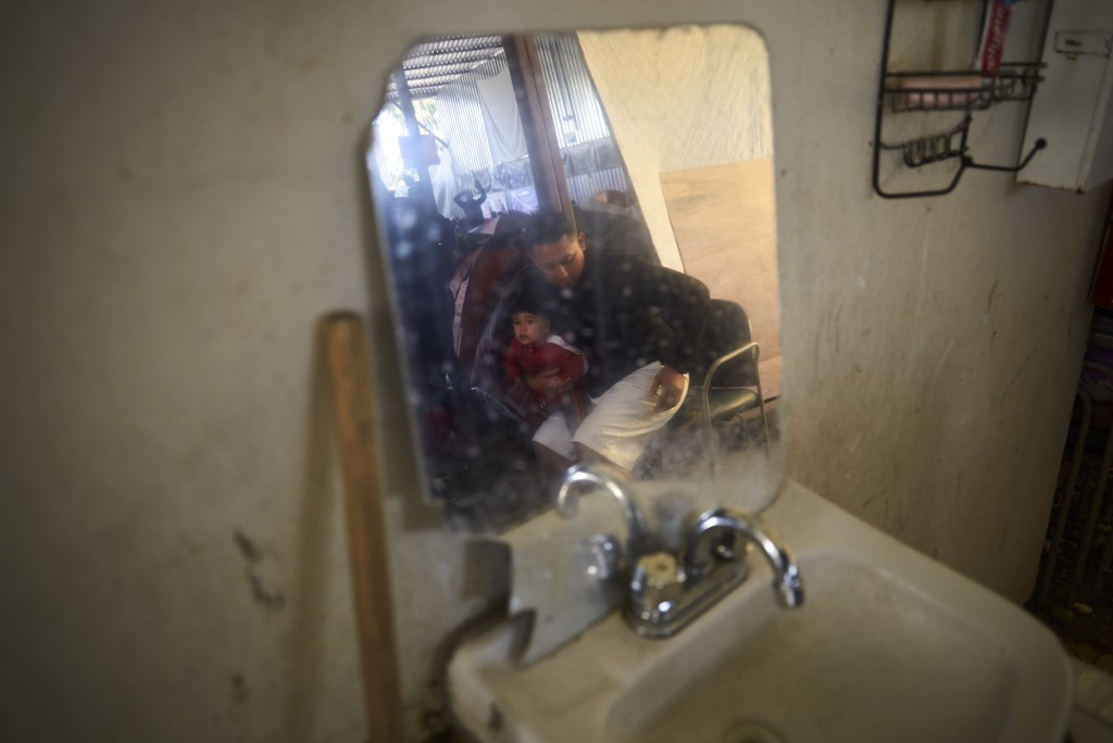 In this March 5, 2019, image, Juan Carlos Perla holds his 10-month-old son, Joshua, reflected in a mirror inside a shelter for migrants in Tijuana, Me