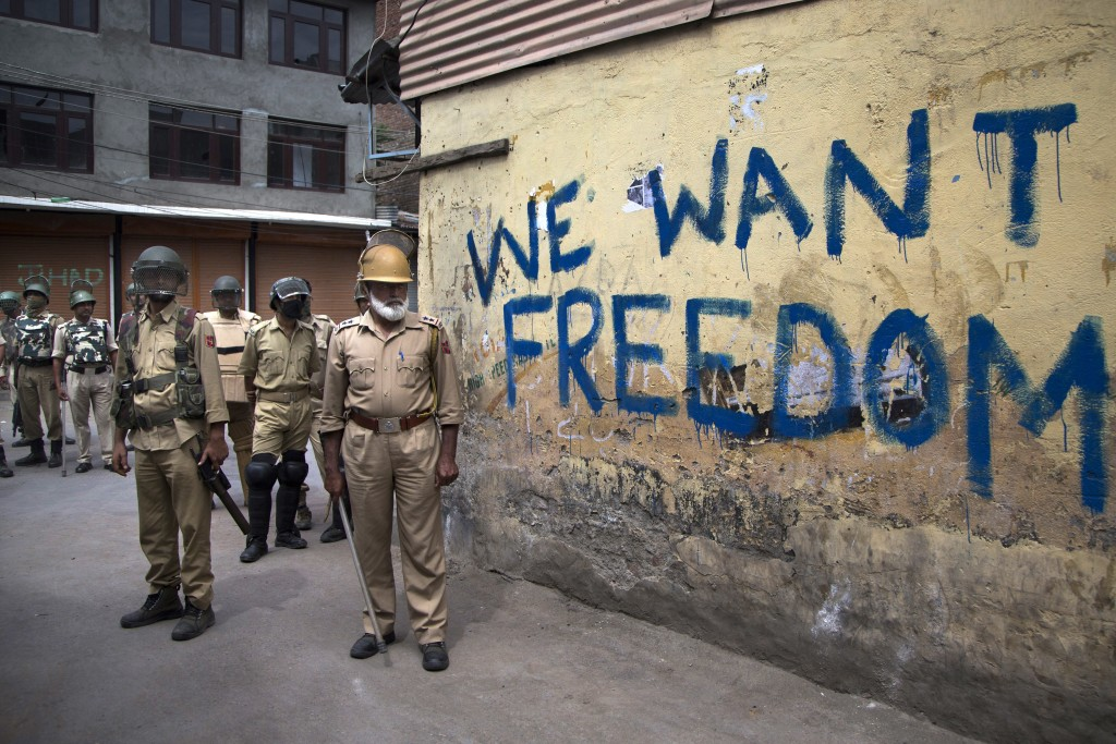 FILE - In this Aug. 12, 2016, file photo, Indian policemen stand guard during a curfew in Srinagar, Indian-controlled Kashmir. Indian Prime Minister N