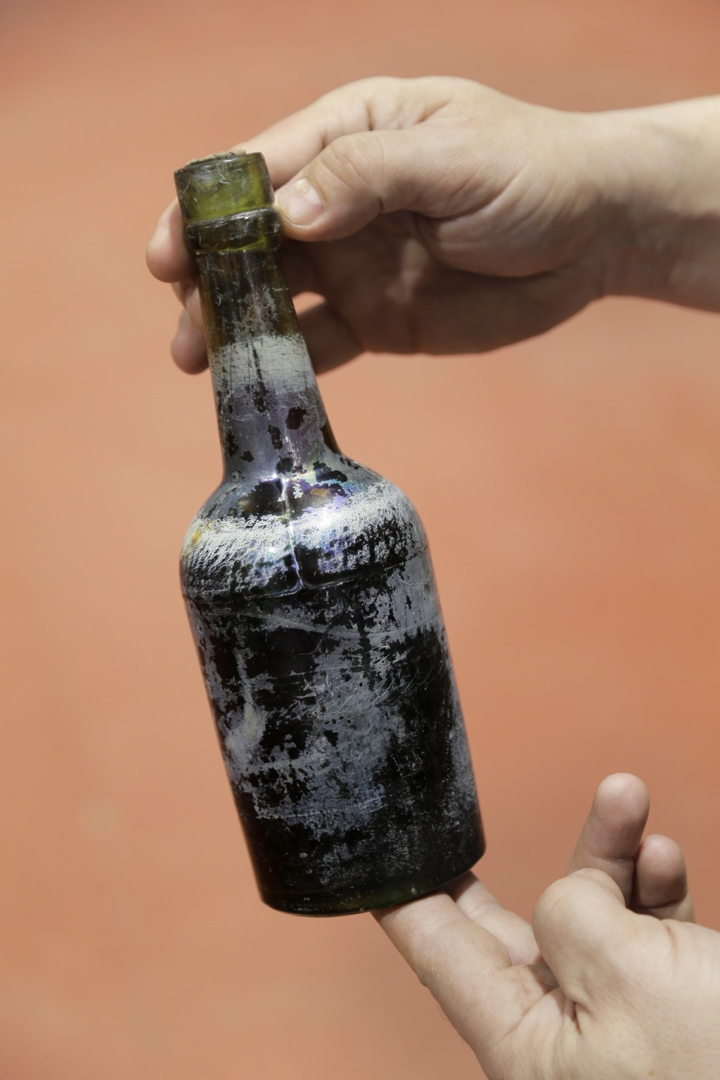 In this March 4, 2019, photo, Jamie Adams displays a bottle of beer recovered from the shipwreck of the SS Oregon at his St. James Brewery in Holbrook