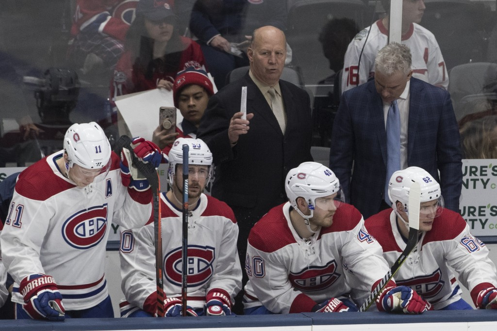 Montreal Canadiens coach Claude Julien, background left, reacts during the third period of the team's NHL hockey game against the New York Islanders,