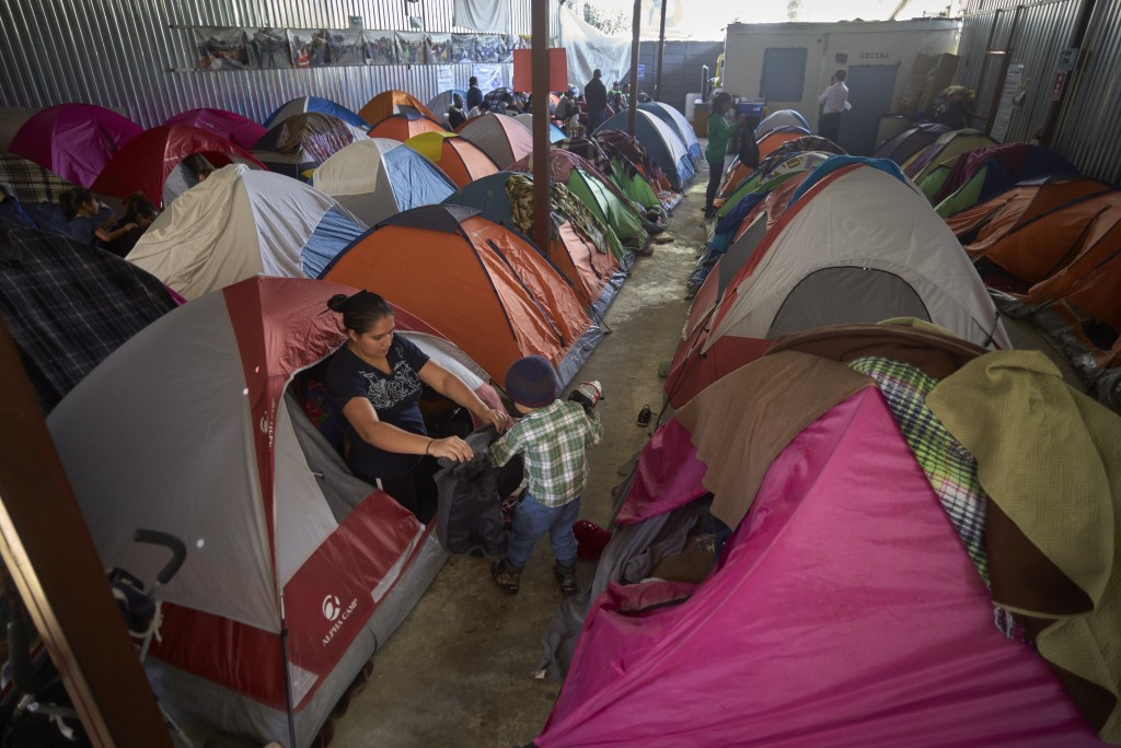 In this March 5, 2019, image, Ruth Aracely Monroy helps her son, Carlos, with his jacket among tents set up inside a shelter for migrants in Tijuana,