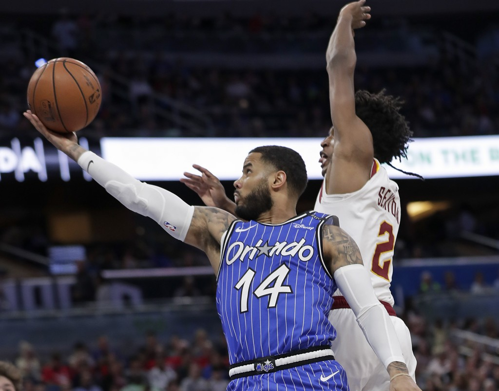 Orlando Magic's D.J. Augustin (14) goes up to shoot past Cleveland Cavaliers' Collin Sexton (2) during the first half of an NBA basketball game, Thurs