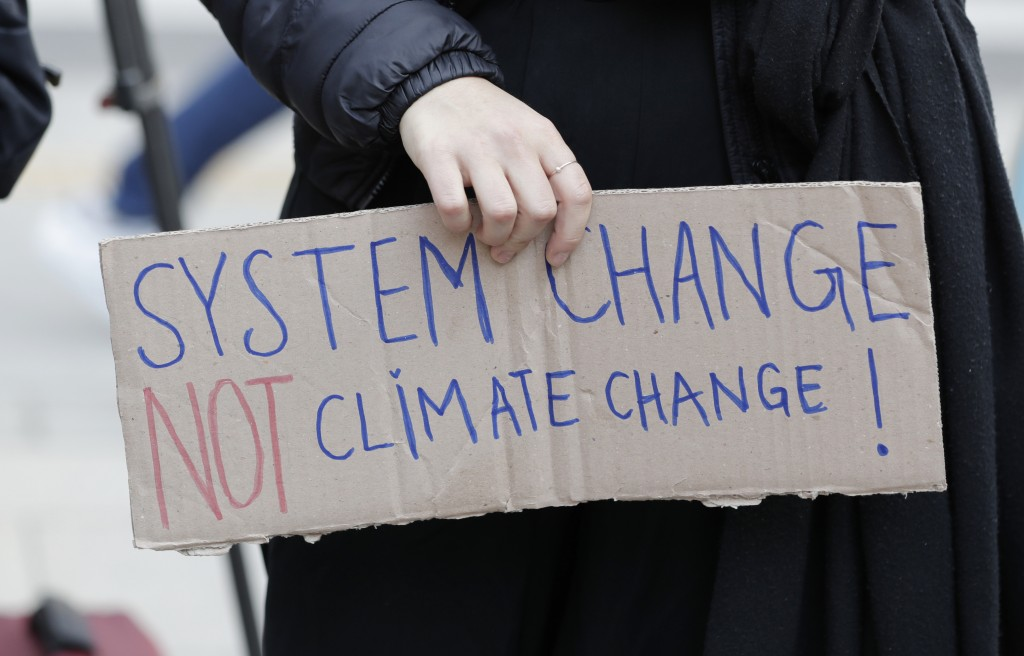 A participant holds a sign during a rally for global climate strike for future in Seoul, South Korea, Friday, March 15, 2019. About 150 students and o