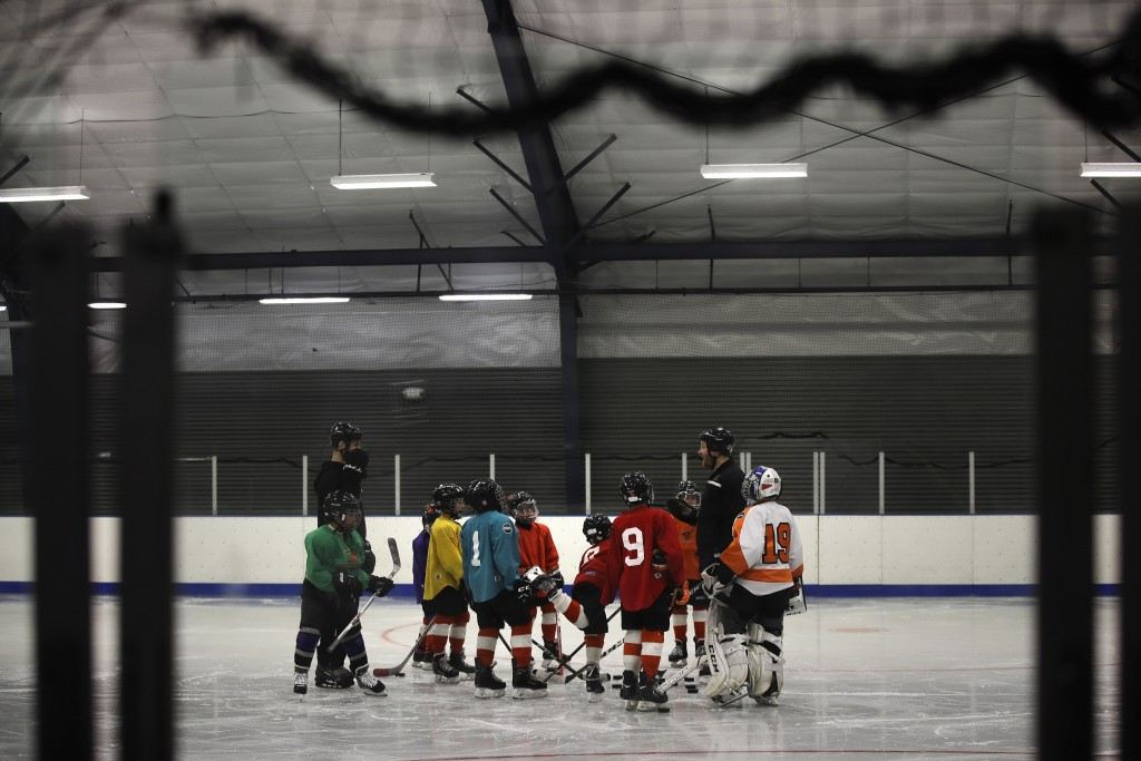 In this Feb. 21, 2019 photo Malakye Johnson (1) gathers with his teammates during a Snider Hockey practice at the Scanlon Ice Rink in Philadelphia. (A