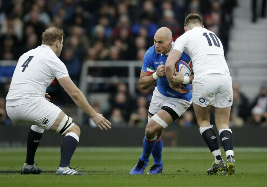 FILE - In this Saturday, March 9, 2019 file photo, Sergio Parisse, center, is tackled by England's Owen Farrell, right, during the Six Nations rugby u
