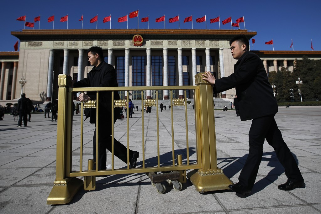 Soldiers in usher uniforms push a barricade as they prepare to close off the Great Hall of the People after the closing session of China's National Pe