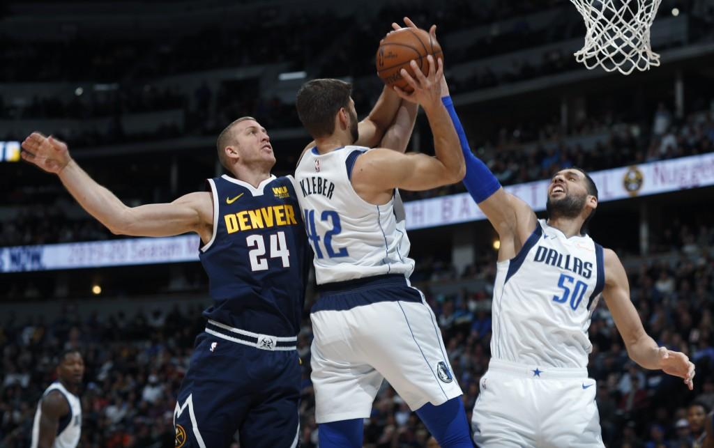 Denver Nuggets forward Mason Plumlee competes for a rebound with Dallas Mavericks forward Maximilian Kleber and center Salah Mejri, right, during the