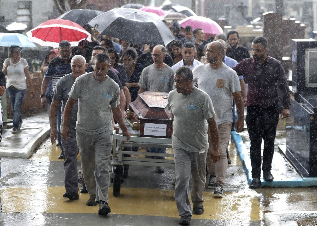 Cemetery employees carry the coffin that contain the remains of 15-year-old Kaio Lucas da Costa Limeira, a victim of the mass shooting at the Raul Bra