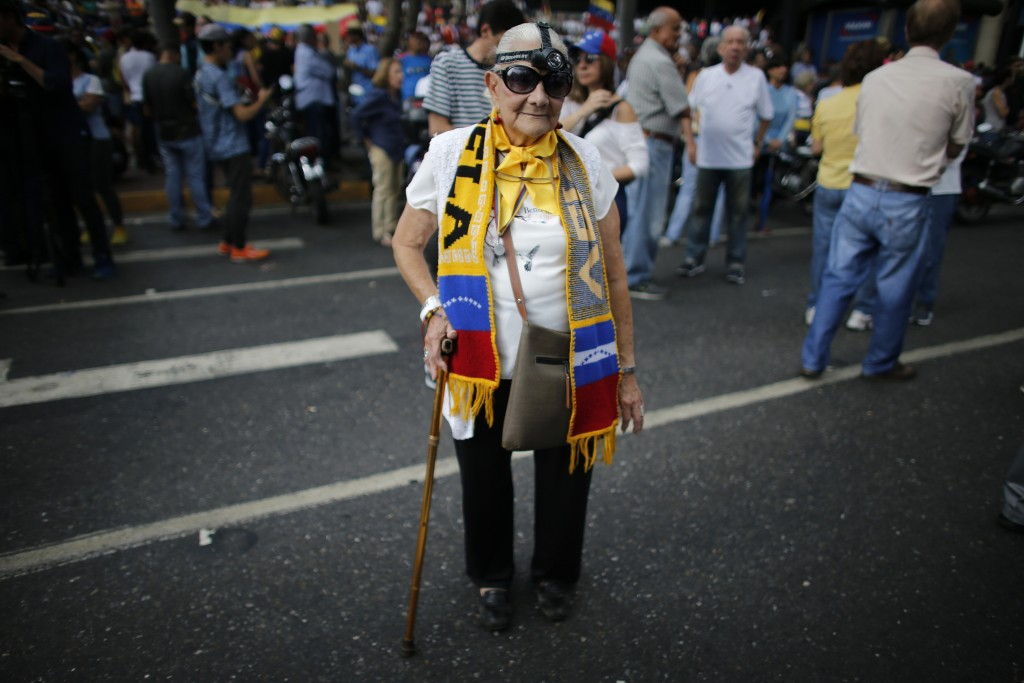 Trina Parry, 83, sporting a headlight headlamp, joins a protest against the government of President Nicolas Maduro, in Caracas, Venezuela, on Tuesday,