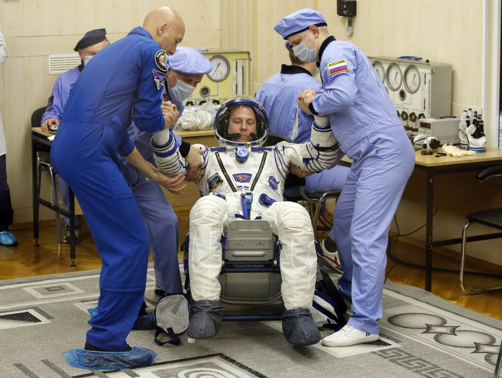 Russian Space Agency experts help U.S. astronaut Nick Hague, member of the main crew of the expedition to the International Space Station (ISS), to st