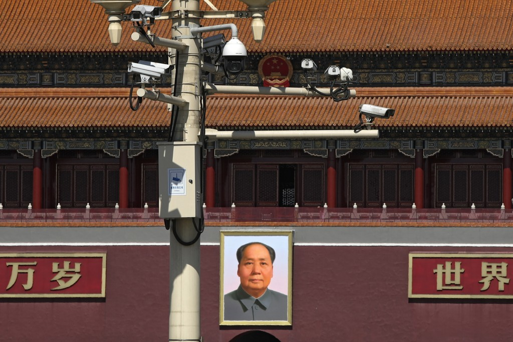 Surveillance cameras are mounted on a lamp post near the large portrait of Chinese leader Mao Zedong at the Tiananmen Gate in Beijing, Friday, March 1