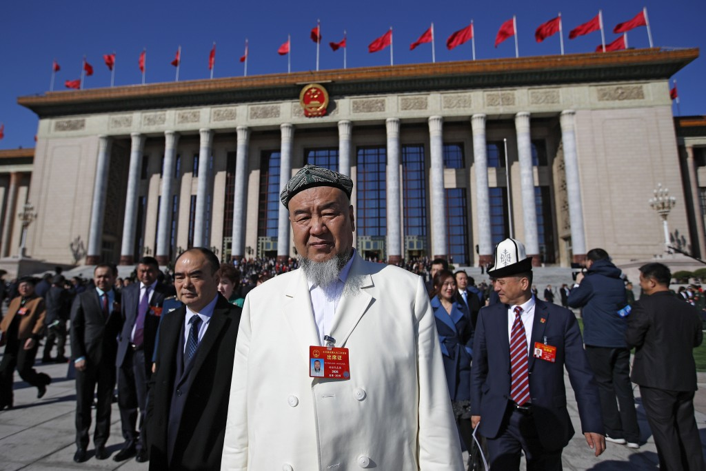 A Xinjiang delegate walks among the delegates as they leave the Great Hall of the People after attending the closing session of China's National Peopl