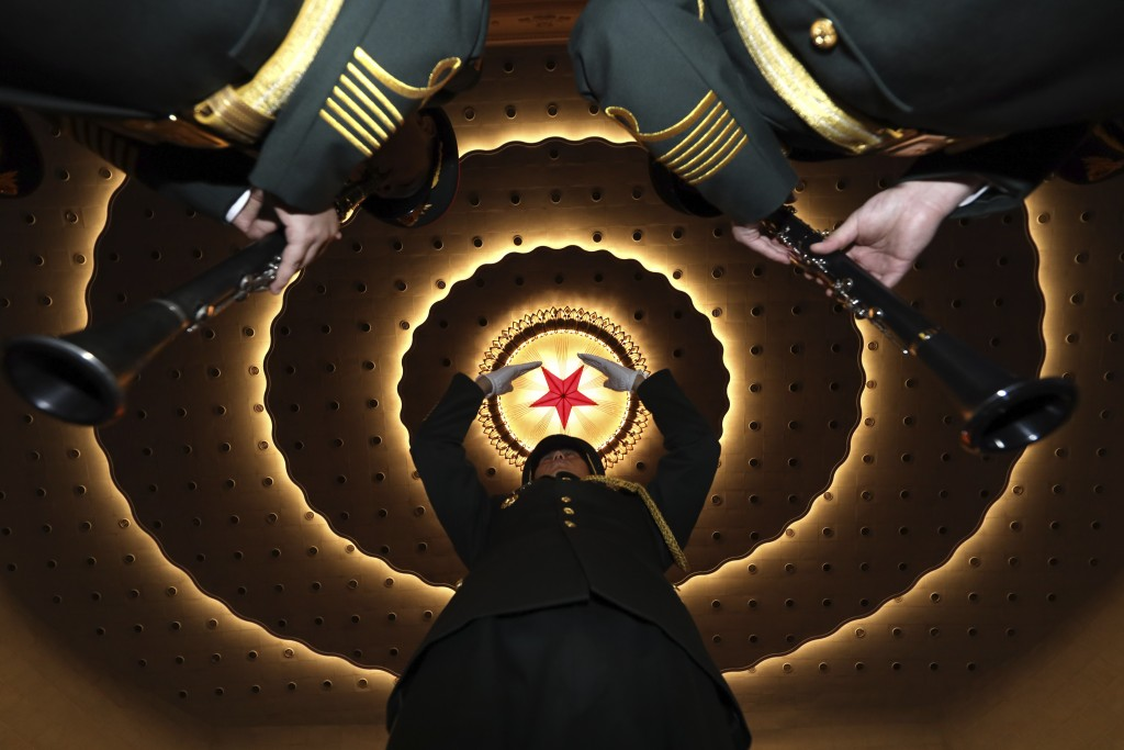 A military band conductor rehearses the band before the closing session of the National People's Congress in Beijing's Great Hall of the People on Fri