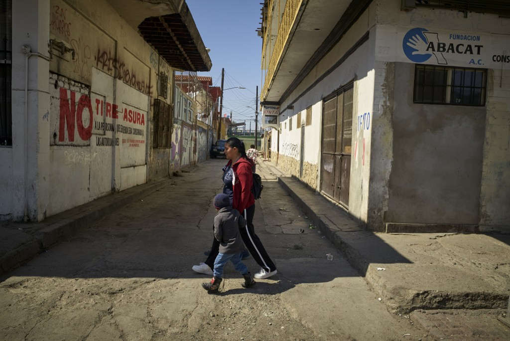 In this March 5, 2019, image, Ruth Aracely Monroy walks with her sons in Tijuana, Mexico. After fleeing violence in El Salvador and requesting asylum