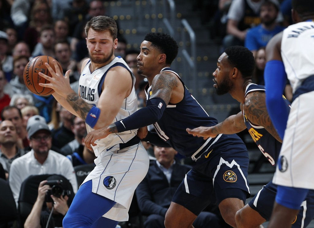 Dallas Mavericks forward Luka Doncic, left, looks to pass the ball as Denver Nuggets guards Gary Harris and Will Barton defend during the first half o