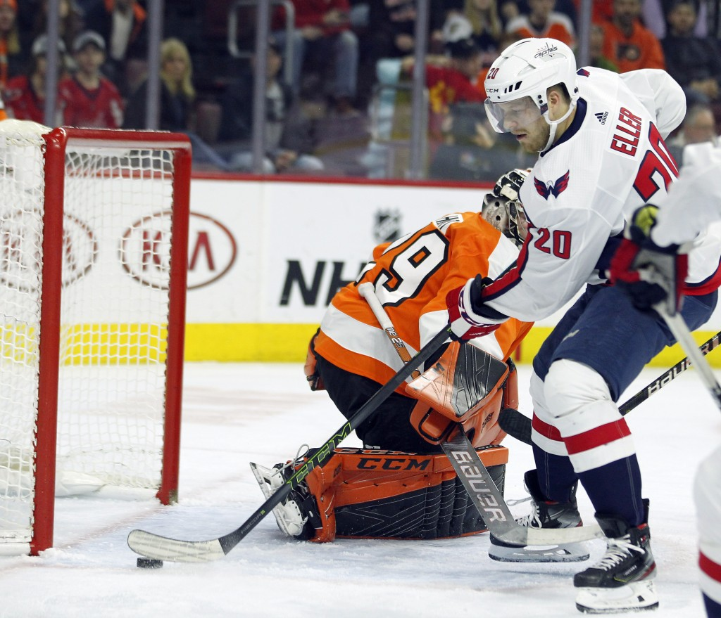 Washington Capitals' Lars Eller gets the puck past Philadelphia Flyers goalie Carter Hart for a goal during the first period of an NHL hockey game Thu