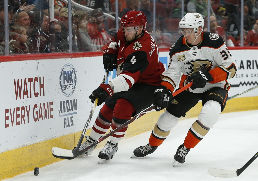 Arizona Coyotes defenseman Niklas Hjalmarsson (4) and Anaheim Ducks right wing Jakob Silfverberg (33) race for the puck in the first period during an