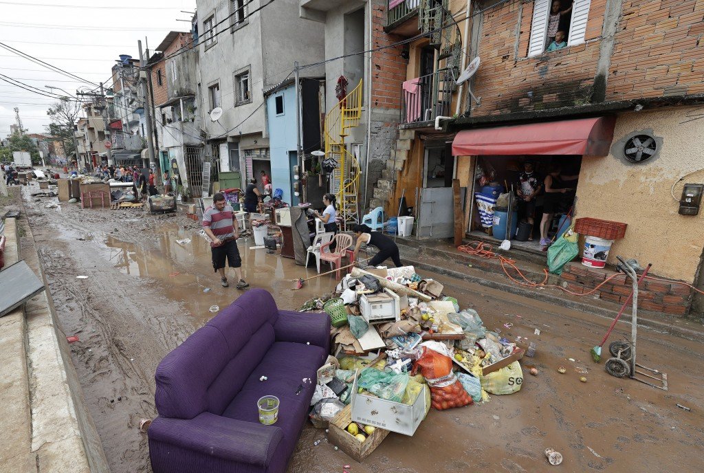 Damaged belongings, spoiled food and soaked furniture are piled up in the street to be taken away after flooding in Sao Paulo, Brazil, on Monday, Marc