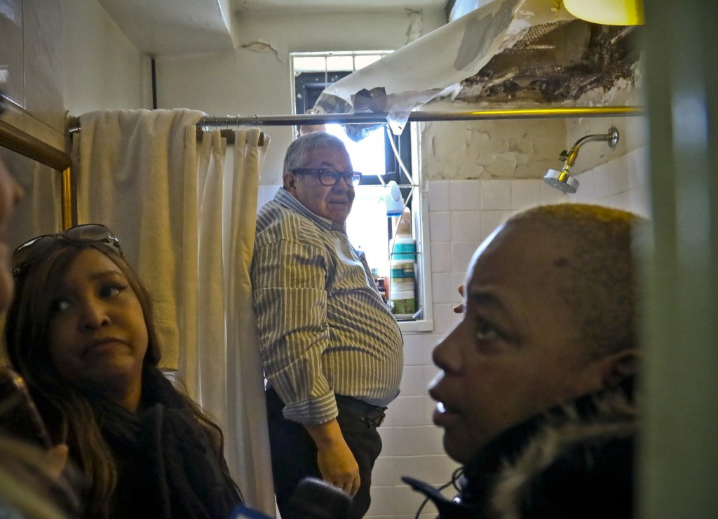 In this March 6, 2019 photo, Luis Pauilno, center, a resident at the New York City Housing Authority's Queensbridge Houses, peels away a makeshift pla