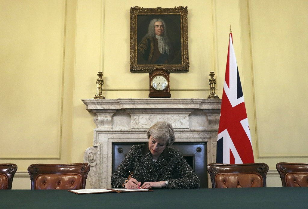 FILE - In this Tuesday March 28, 2017 file photo, Britain's Prime Minister Theresa May, sitting below a painting of Britain's first Prime Minister Rob
