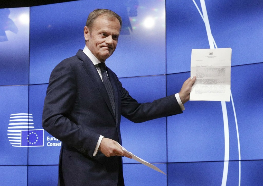 FILE- In this Wednesday, March 29, 2017 file photo, EU Council President Donald Tusk holds British Prime Minister Theresa May's Brexit letter in notic
