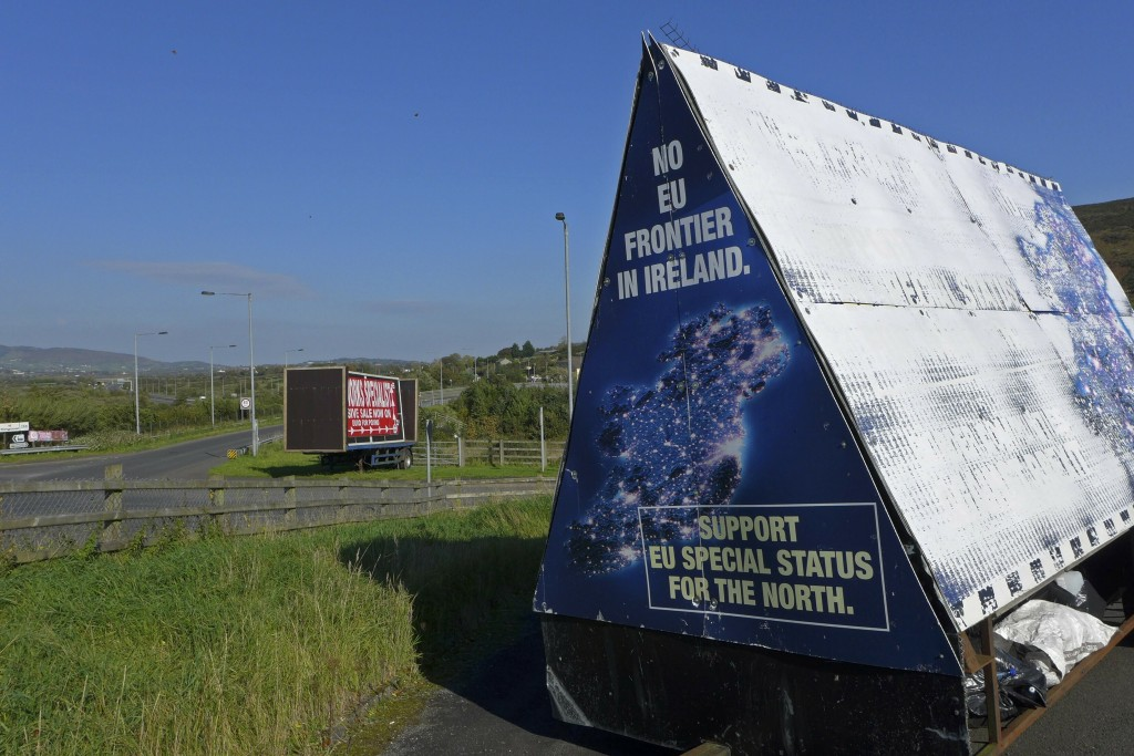 "FILE - In this file photo taken on Wednesday, Oct. 10, 2018, a sign in a parking lot of a cemetery reads: ""No EU border in Ireland"" near Carrickcarnan"