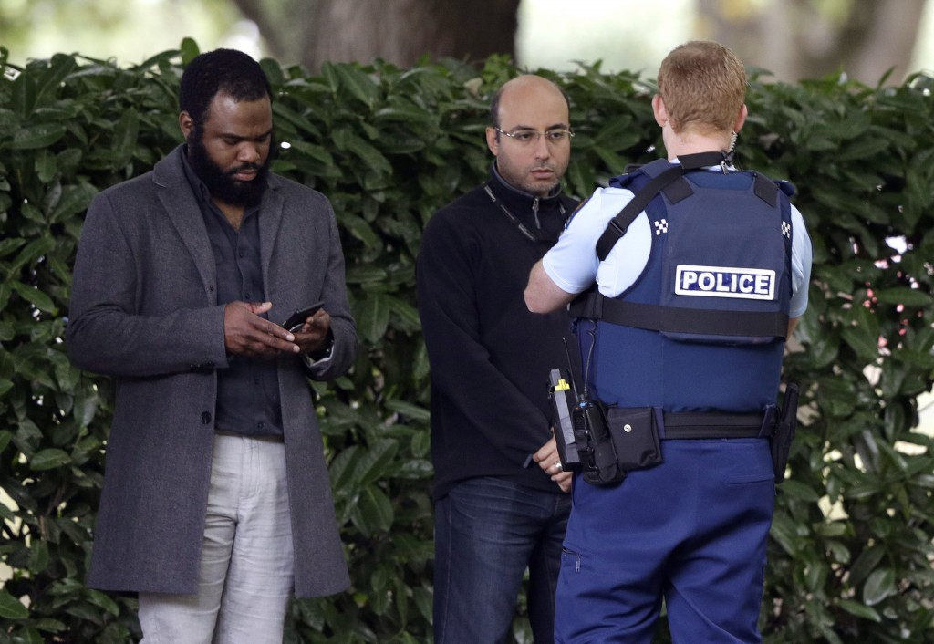 A police officer photographs witnesses near a mosque in central Christchurch, New Zealand, Friday, March 15, 2019. Multiple people were killed in mass