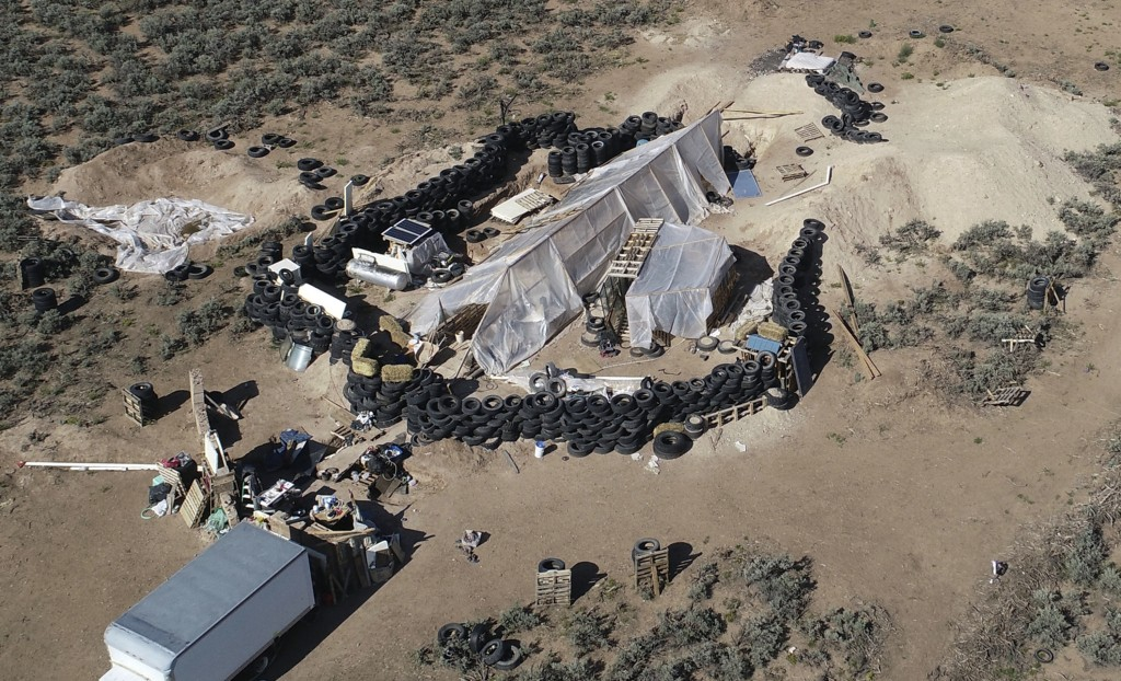 FILE - This Aug. 10, 2018, file photo shows a ramshackle compound in the desert area of Amalia, N.M. The five men and women found living in a ramshack