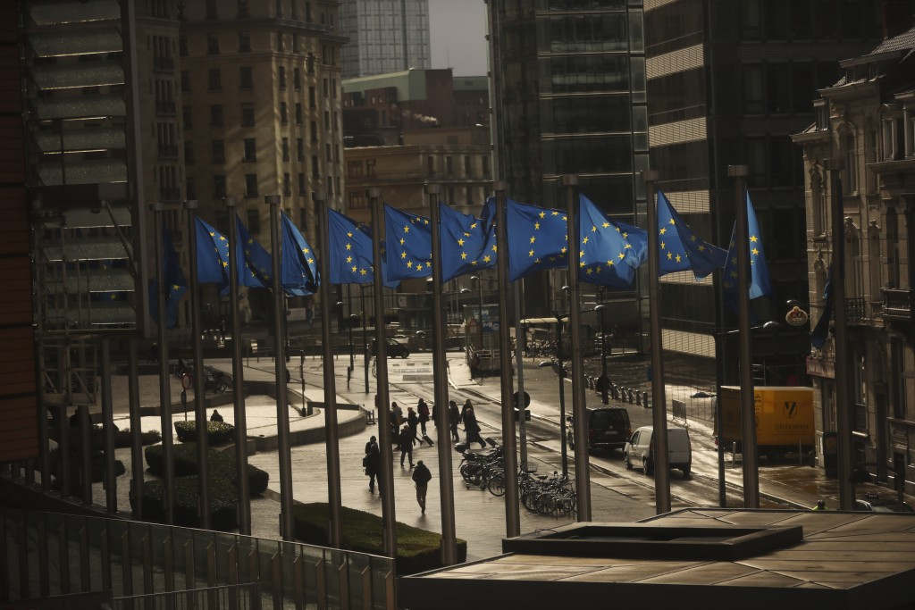 People walk past European Union flags placed outside the European Commission headquarters in Brussels, Thursday, March 14, 2019. Britons in Brussels a