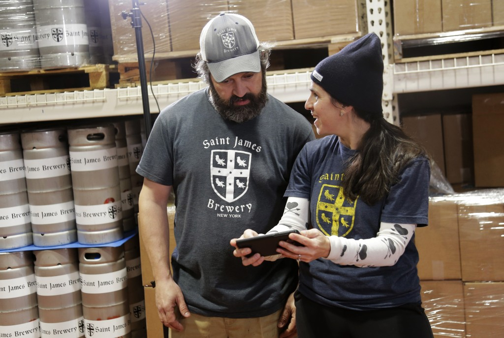 In this March 4, 2019, photo, Jamie Adams and his wife Rachel Adams look at an image of a banner for their new beer, Deep Ascent, at their St. James B
