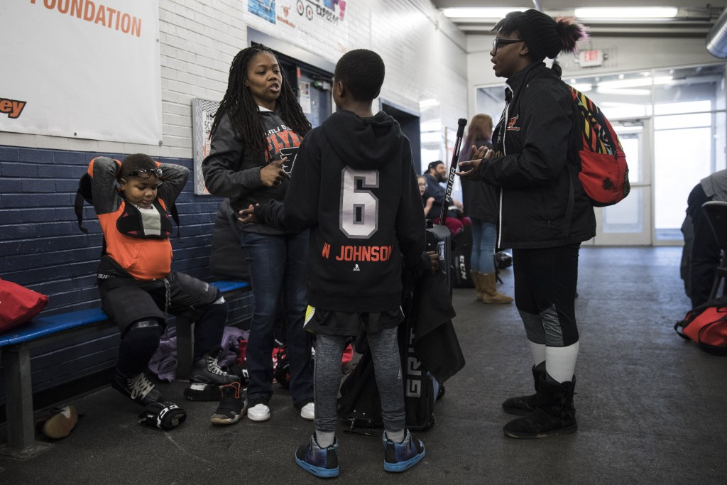 In this Feb. 21, 2019 photo April Johnson, center left, speaks with children Malakye, center, and Wylla as her other son Logan, left, puts on his pads