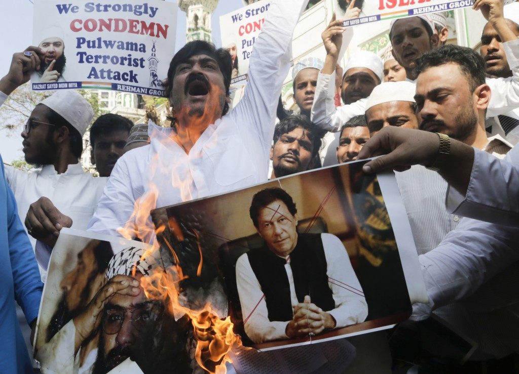 FILE - In this Feb. 15, 2019, file photo, Indian muslims burn posters of Pakistani prime minister Imran Khan, center, and Jaish-e-Mohammed leader Maso