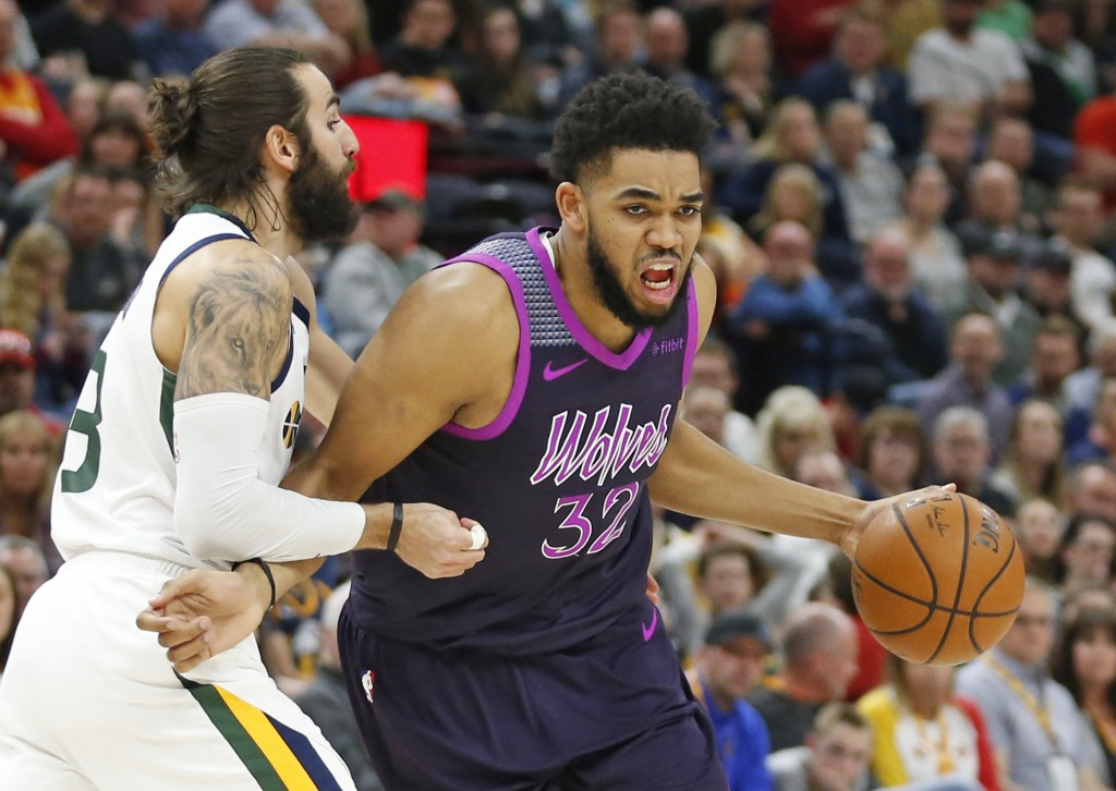 Minnesota Timberwolves center Karl-Anthony Towns (32) drives around Utah Jazz guard Ricky Rubio, left, in the first half during an NBA basketball game