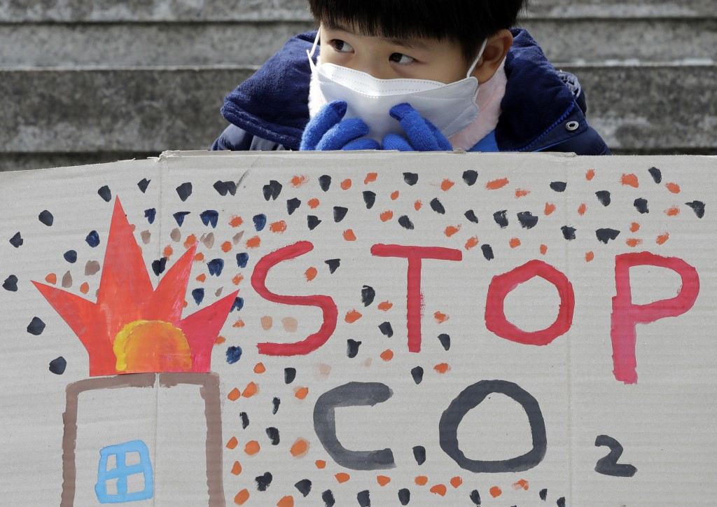 A boy wearing a mask sits behind a banner during a rally for global climate strike for future in Seoul, South Korea, Friday, March 15, 2019. About 150...