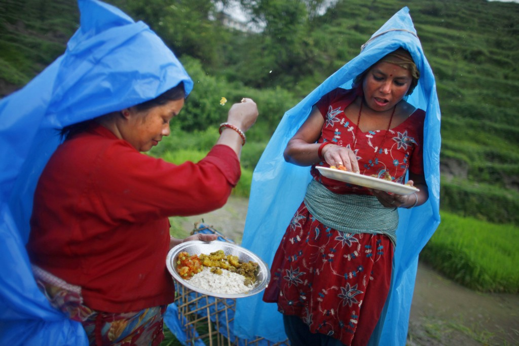 FILE - In this June 30, 2014 file photo, a farmer, left, ritualistically offers a small portion of food to god before eating her lunch while working a