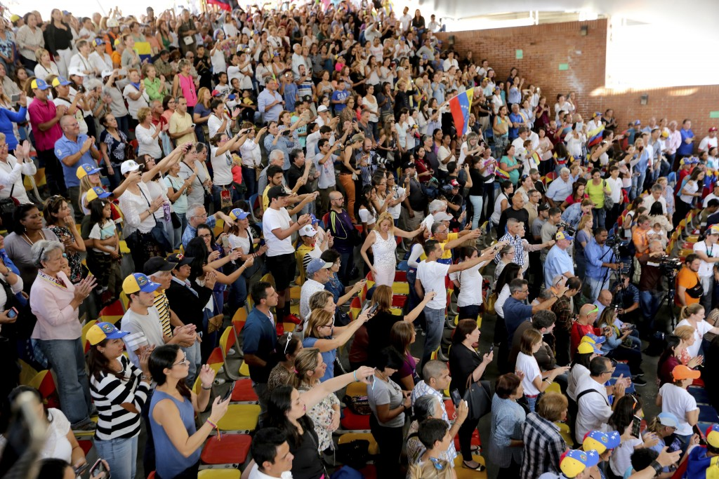Supporters of the National Assembly President Juan Guaido, cheer for him during a meeting with residents in the Hatillo municipality of Caracas, Venez