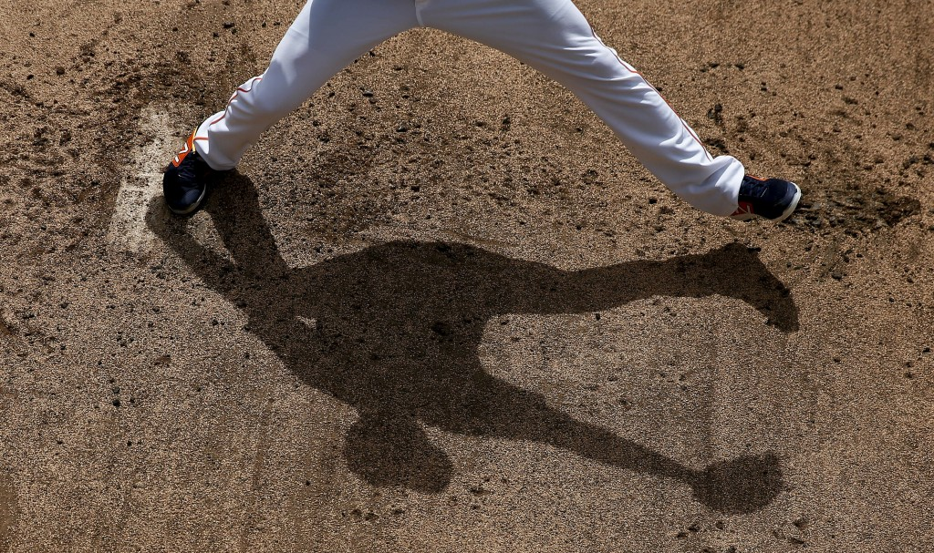 Houston Astros' Collin McHugh casts a shadow as he throws in the bullpen before an exhibition spring training baseball game against the Miami Marlins