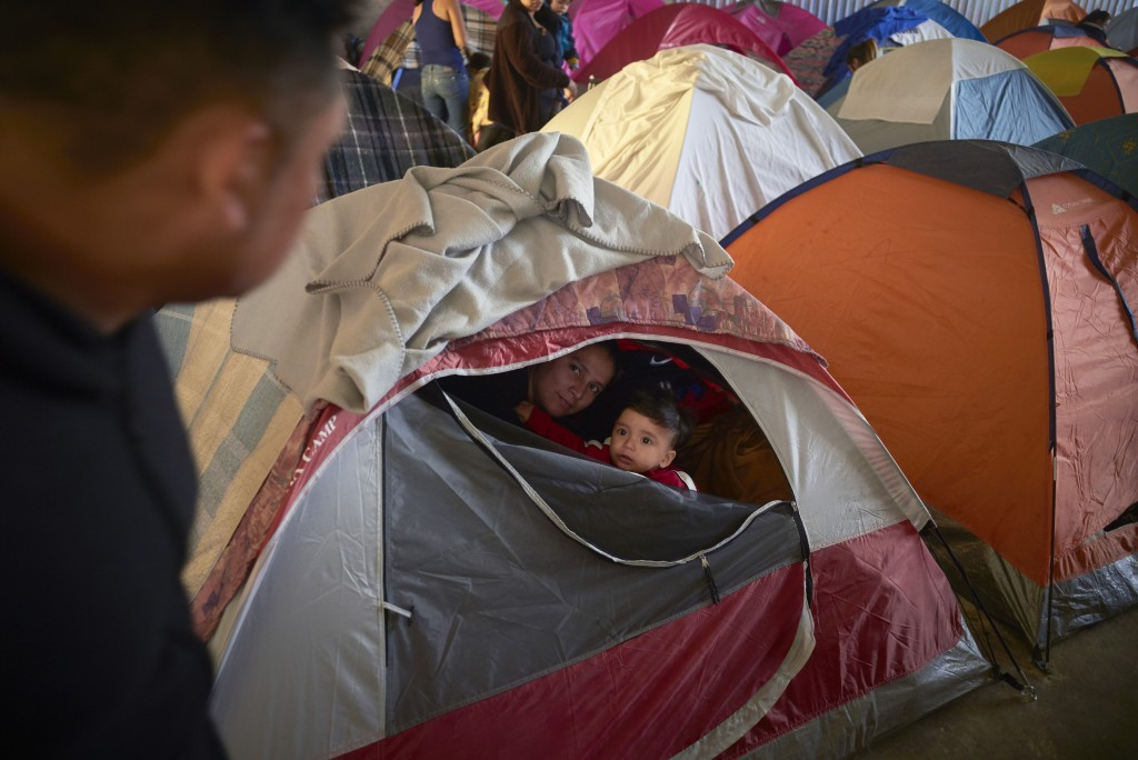 In this March 5, 2019, image, Ruth Aracely Monroy, center, looks out of the family's tent alongside her 10-month-old son, Joshua, as her husband, Juan