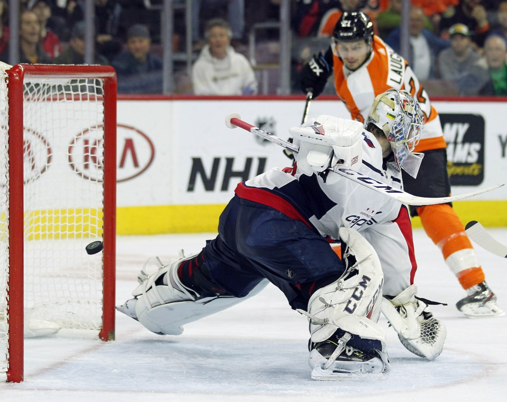 Washington Capitals' Braden Holtby fails to stop the shot as Philadelphia Flyers' Scott Laughton, rear, scores during the second period of an NHL hock