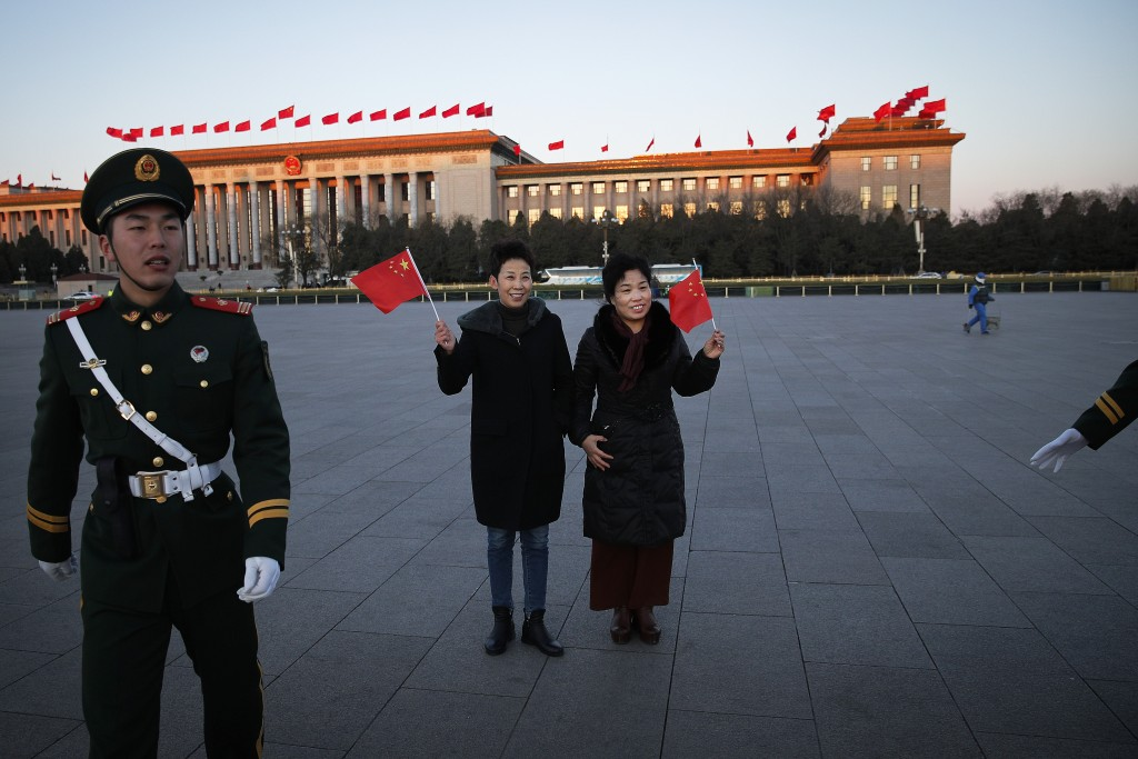Chinese women pose with national flags in front of the Great Hall of the People as paramilitary policemen try to clear Tiananmen Square after the dail