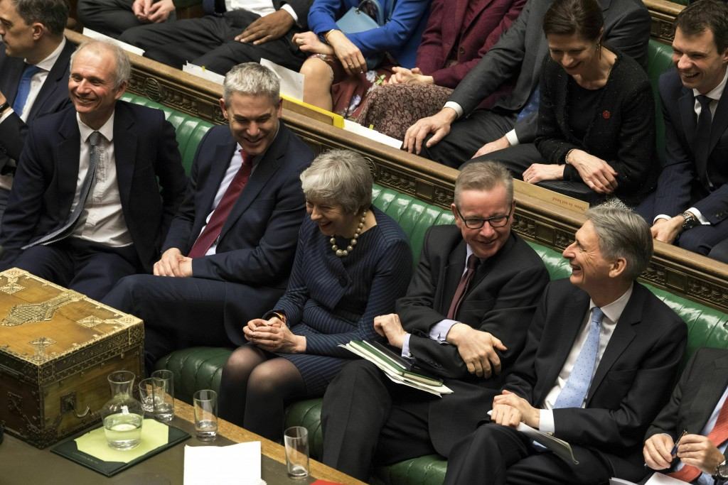 In this handout photo provided by UK Parliament, Britain's Prime Minister Theresa May, centre, laughs during the Brexit debate in the House of Commons