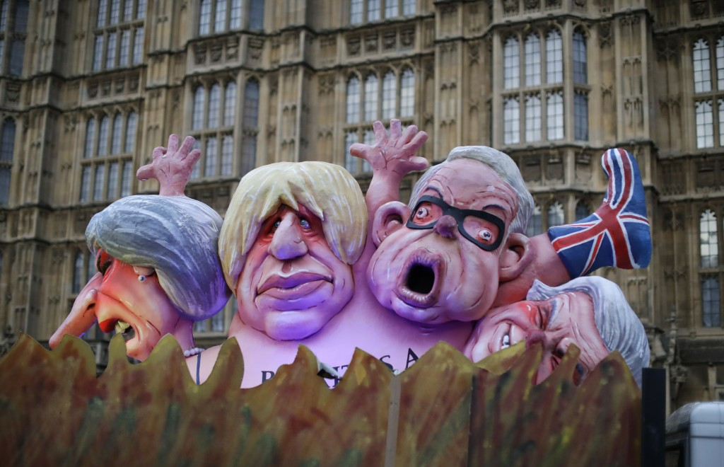 Effigies of British politicians from left, Prime Minister Theresa May, Boris Johnson and Michael Gove are driven on a truck by anti-Brexit, remain in
