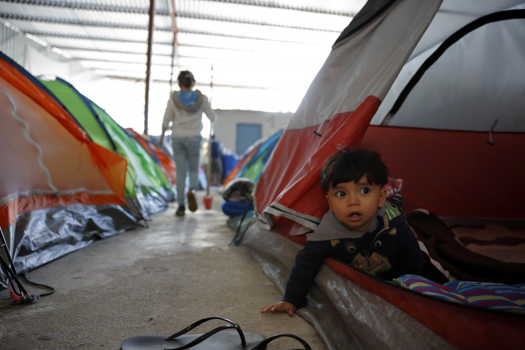 In this March 12, 2019, image, 10-month-old Joshua Perla looks out from the family's tent in a shelter for migrants in Tijuana, Mexico. Asylum seekers