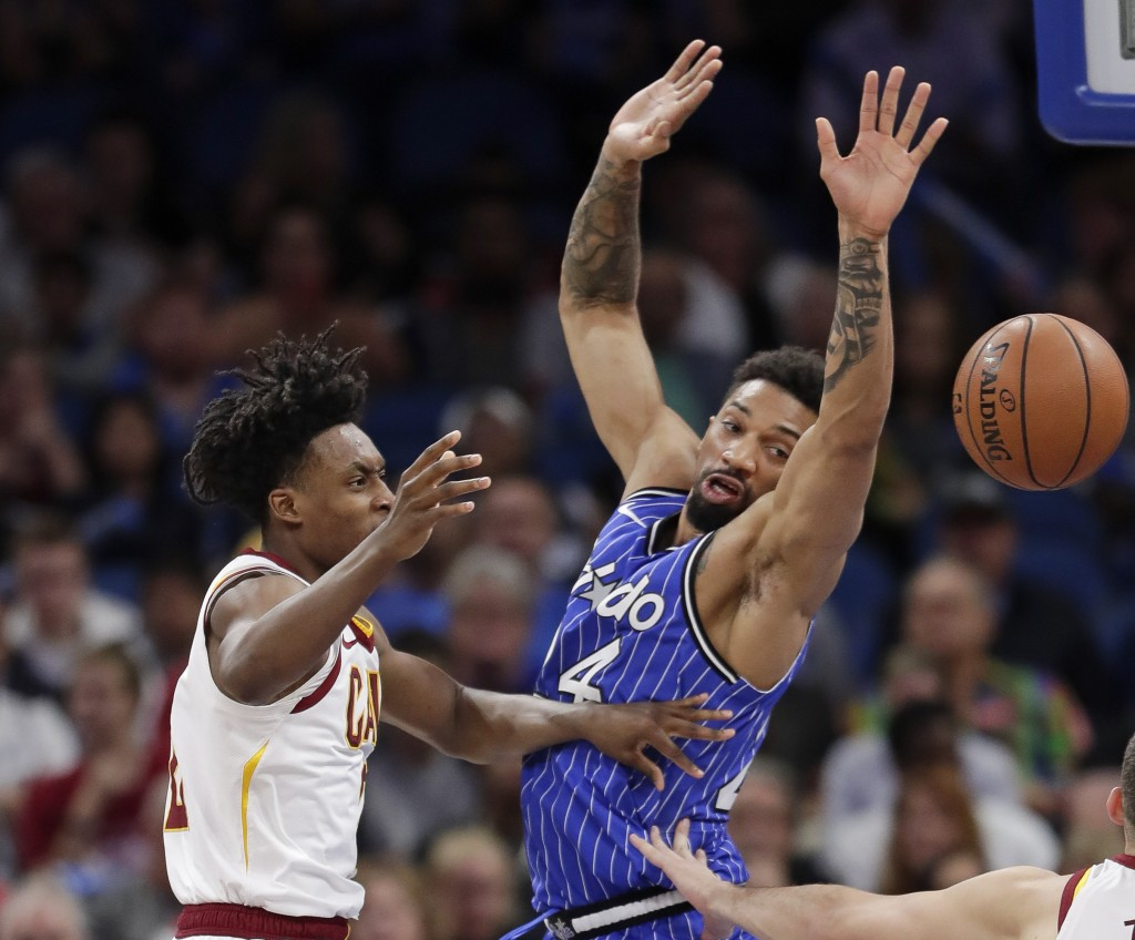Cleveland Cavaliers' Collin Sexton, left, passes the ball around Orlando Magic's Khem Birch, right, during the first half of an NBA basketball game, T