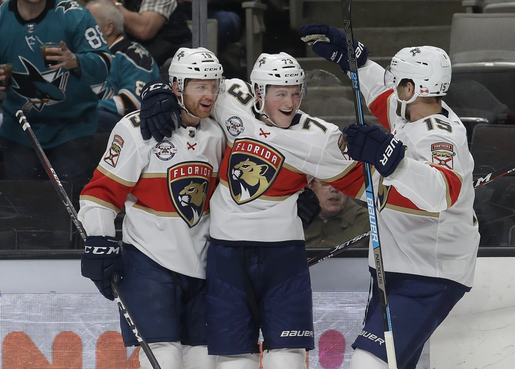 Florida Panthers left wing Dryden Hunt, center, is congratulated by defenseman Mike Matheson, left, and center Riley Sheahan after scoring a goal agai