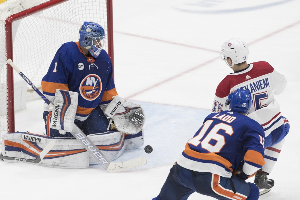 New York Islanders goaltender Thomas Greiiss, left, makes a save against Montreal Canadiens center Jesperi Kotkaniemi, upper right, during the third p