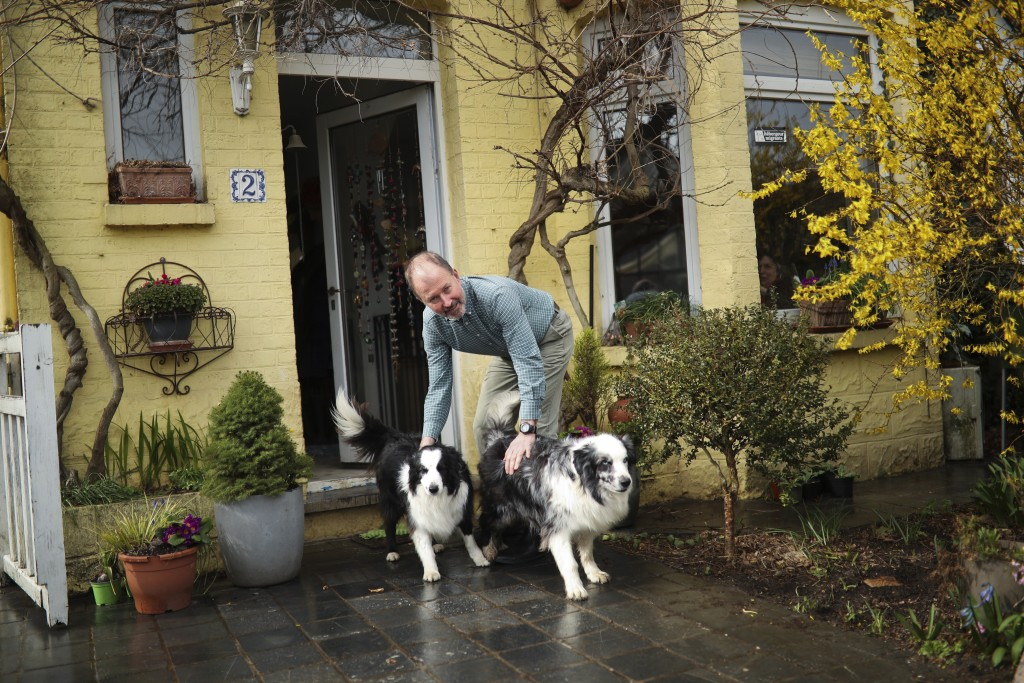 In this photo taken on Wednesday, March 13, 2019, British lobbyist Brian O'Riordan poses with his dogs in his house in Rixensart, outside Brussels. Br
